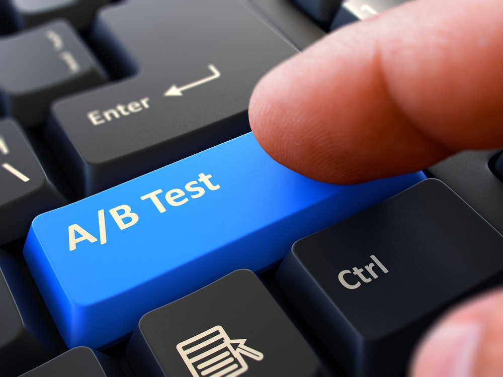 AB Test - Written on Blue Keyboard Key. Male Hand Presses Button on Black PC Keyboard. Closeup View. Blurred Background.