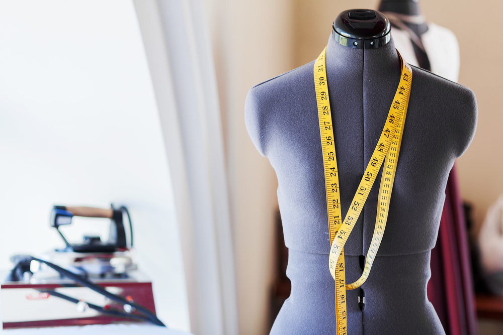 Black dummy with measuring tape in tailors studio-1