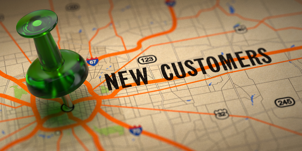 New Customers Concept - Green Pushpin on a Map Background with Selective Focus.