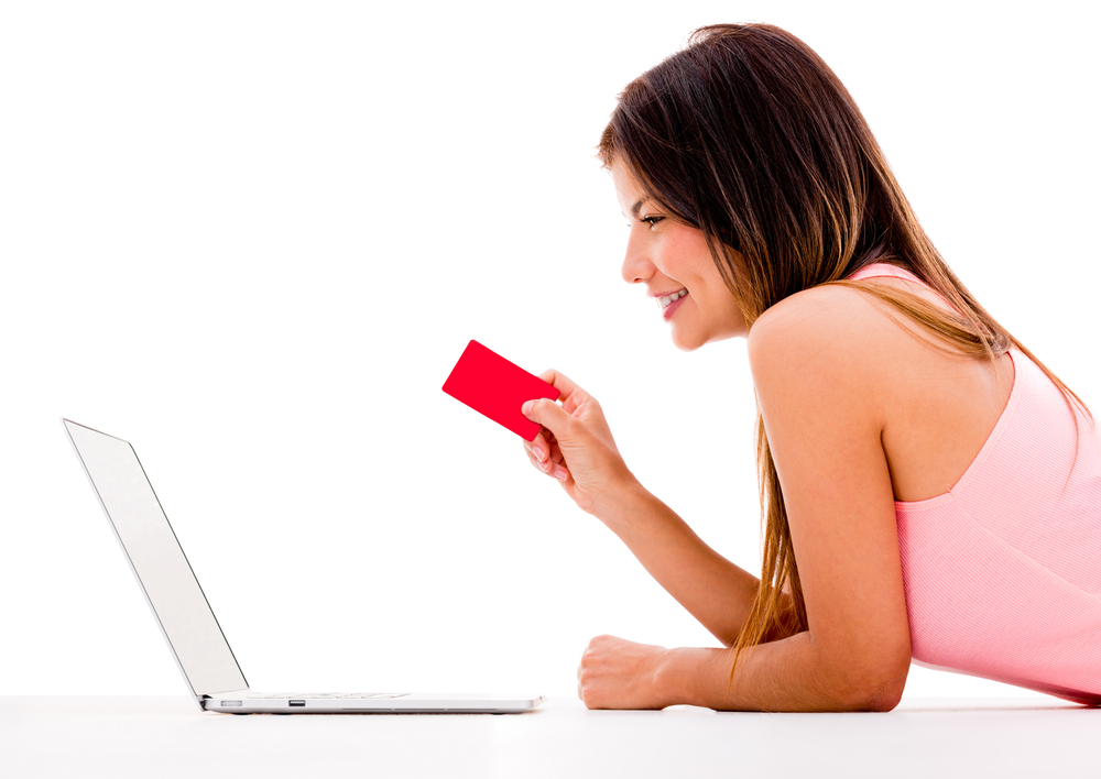Woman online shopping with her laptop - isolated over white
