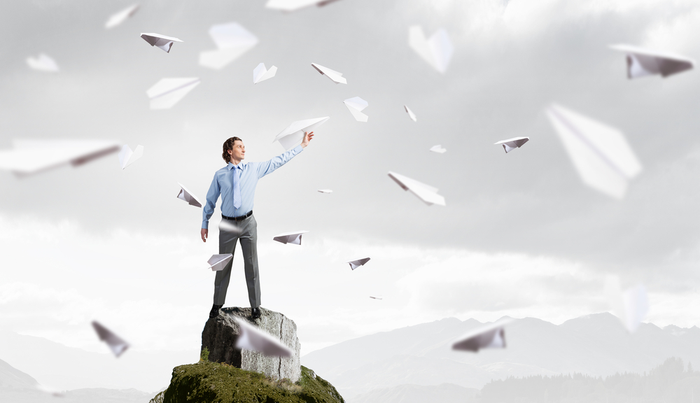Young businessman on rock top with paper plane in hand